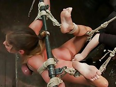 Sexy milf brunette's hands and legs are tied and suspended naked in the air. Her oily boobs are also tied. Her legs are made widened so that the girl can easily penetrate in her pussy. She put her fingers deep in brunette's cunt.